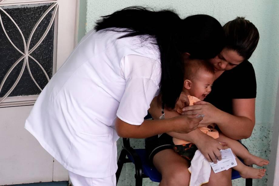 Centenas de pessoas, entre homens, mulheres e crianças, fazem fila, em posto de saúde em Mairiporã, para serem vacinadas contra a febre amarela - 11/01/2018