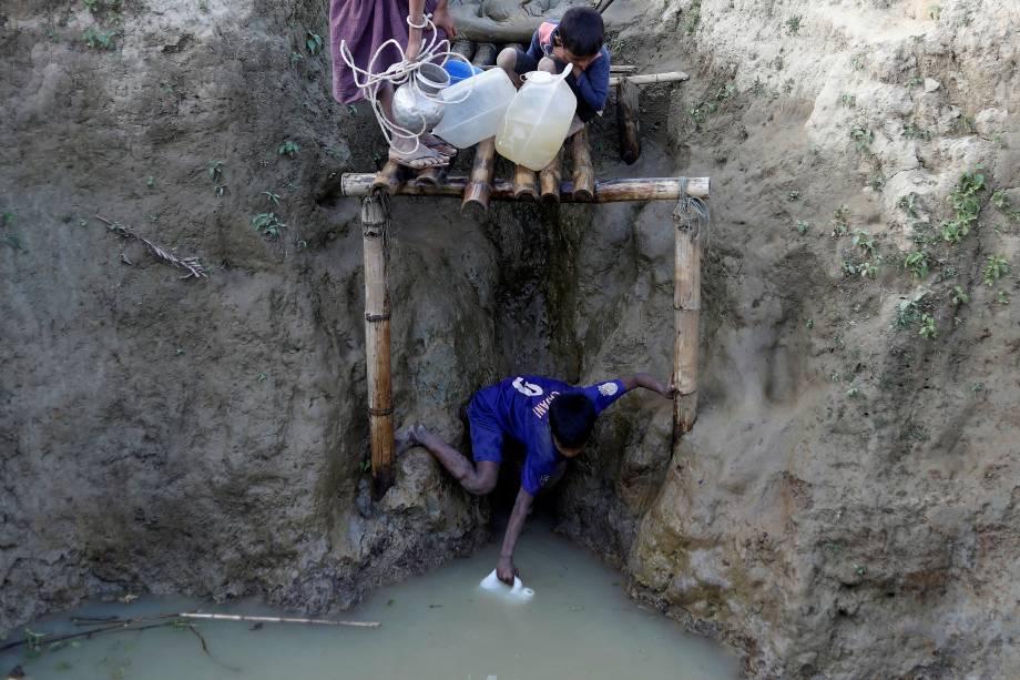 Um refugiado rohingya se estica para encher um galão com água em um poço no campo de refugiados de Unchiparang, perto de Cox's Bazar, no Bangladesh - 11/01/2018