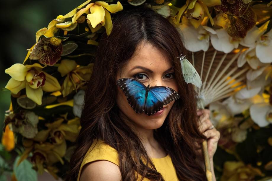 Uma borboleta morpho azul pousa no rosto da modelo Jessie Baker durante a exposição Butterflies in The Glasshouse RHS Garden Wisley em Woking, na Inglaterra - 12/01/2018