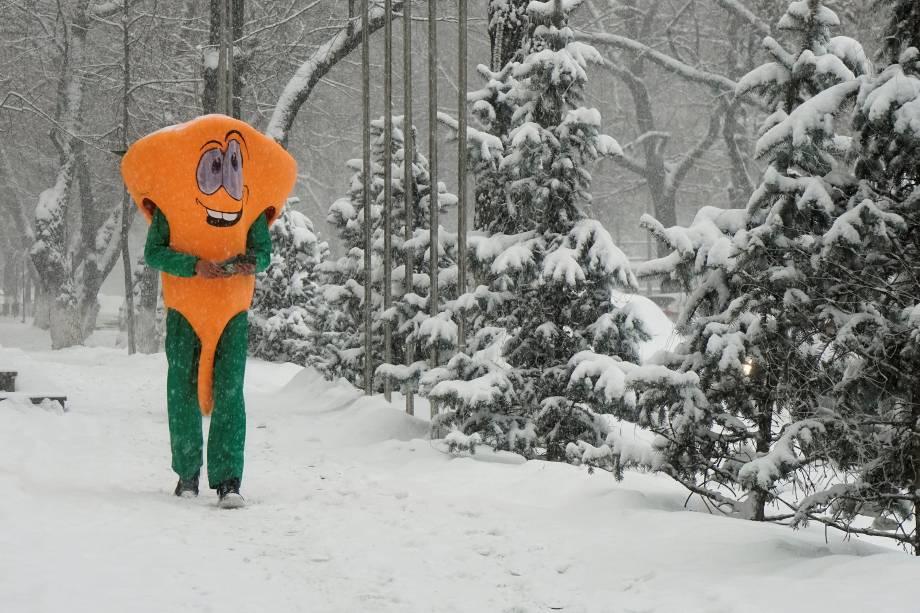 Um homem vestido com uma fantasia usada para promover o restaurante em que trabalha é visto andando durante uma queda de neve em Almaty, no Cazaquistão - 11/01/2018