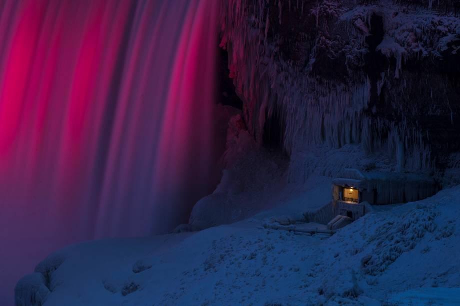Um dos pontos de observação das Cataratas do Niagara, em Ontario, no Canadá, é visto coberto de gelo. Ao lado, luzes iluminam a queda d'água - 10/01/2018