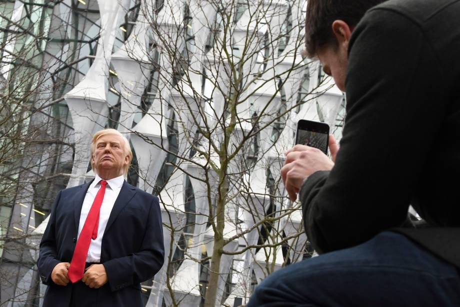 Pedestres tiram fotos de uma estátua de cera Madame Tussauds do presidente Donald Trump, do lado de fora da nova embaixada dos Estados Unidos em Embassy Gardens, no sudoeste de Londres - 12/01/2018