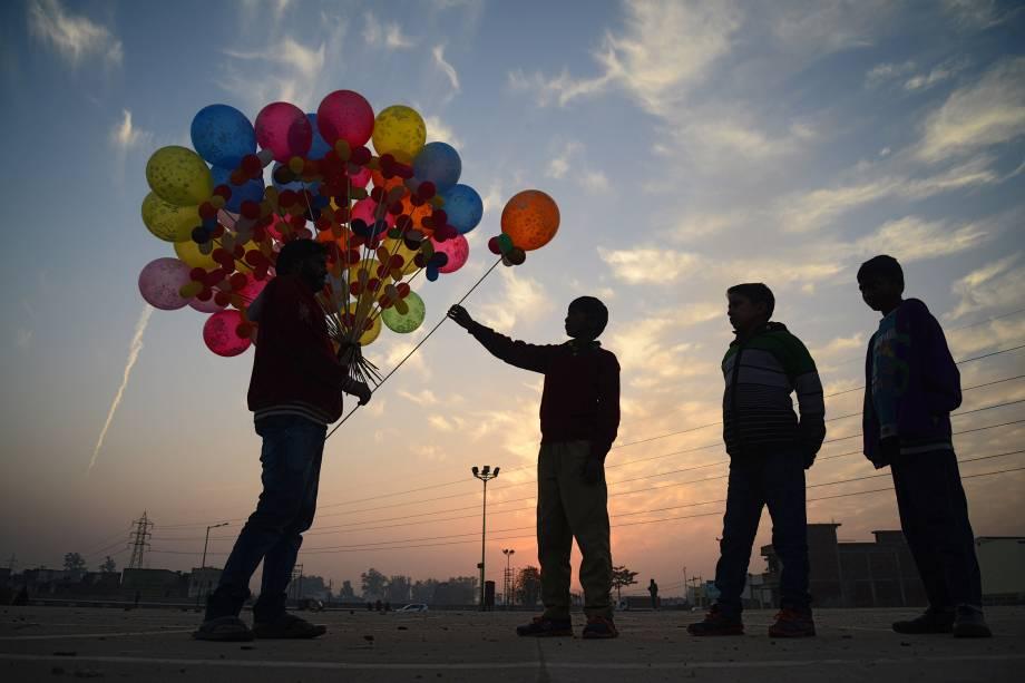 Crianças compram balões de um vendedor ambulante em Jalandhar na Índia - 10/01/2018