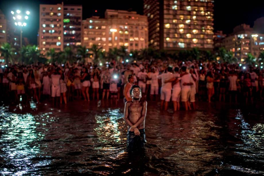 Garoto comemora a chegada do ano novo destacado da multidão, no mar da praia de Copacabana, no Rio de Janeiro - 01/01/2018