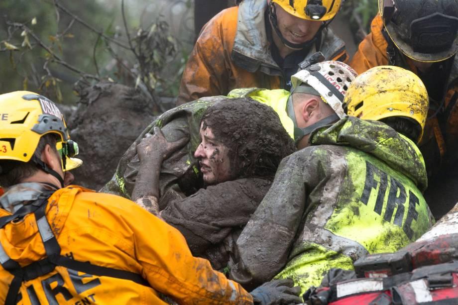 Equipe de emergência carrega uma mulher resgatada de uma casa em ruínas após deslizamento de terra em Montecito, na Califórnia - 09/01/2018