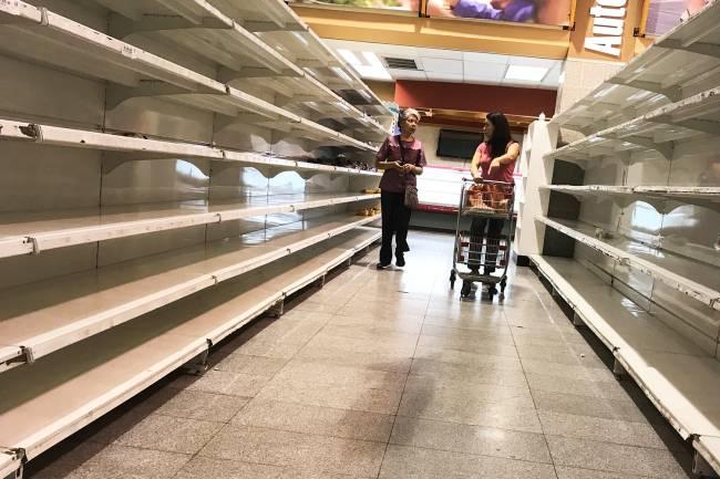 Mulheres caminham próximas de prateleiras vazias de supermercado em Caracas, na Venezuela - 09/01/2018