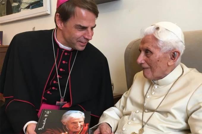 O bispo Stefan Oster entrega uma cópia da biografia ao papa emérito Bento XVI, em outubro de 2017