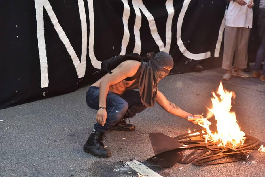 Manifestante coloca fogo em catraca de papel, durante protesto contra aumento da tarifa, em São Paulo