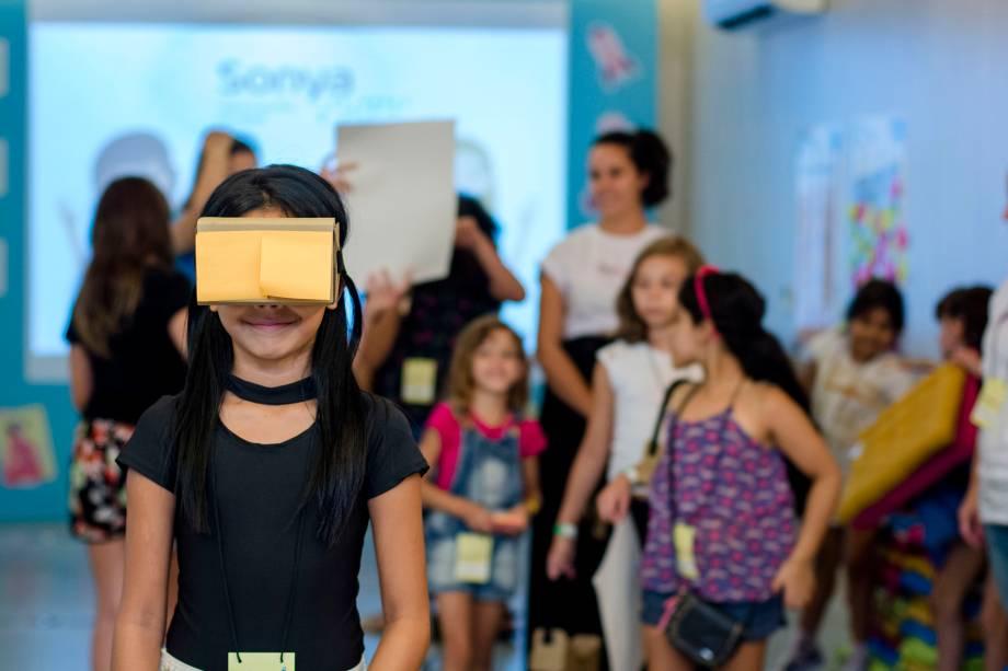 Garota brinca com óculos de realidade virtual feito com papelão e lente descartável