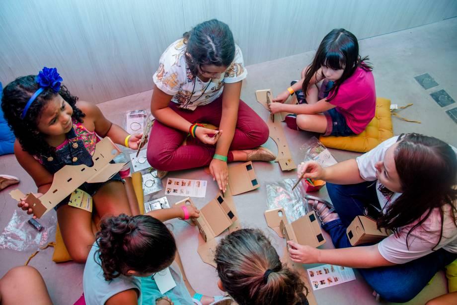 Crianças montam óculos de realidade virtual de papelão e lente descartável