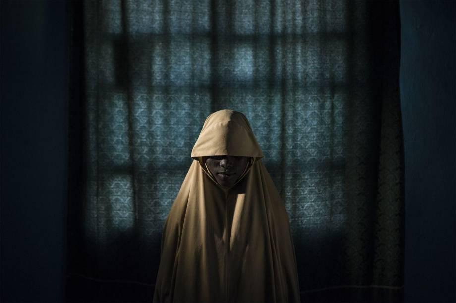 Aisha, de 14 anos, representada em um retrato na cidade de Maiduguri, estado de Borno, na Nigéria em 21 de setembro de 2017. Aisha foi sequestrada pelo grupo Boko Haram que então lhe atribuiu uma missão de atentado suicida. Depois que ela ficou amarrada com explosivos, encontrou ajuda em vez de se explodir junto com quem estaria ao seu lado