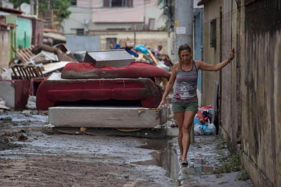 Mulher anda no meio-fio em uma rua cheia de móveis destruídos após uma inundação no bairro de Bonsucesso do Rio de Janeiro - 15/02/2018