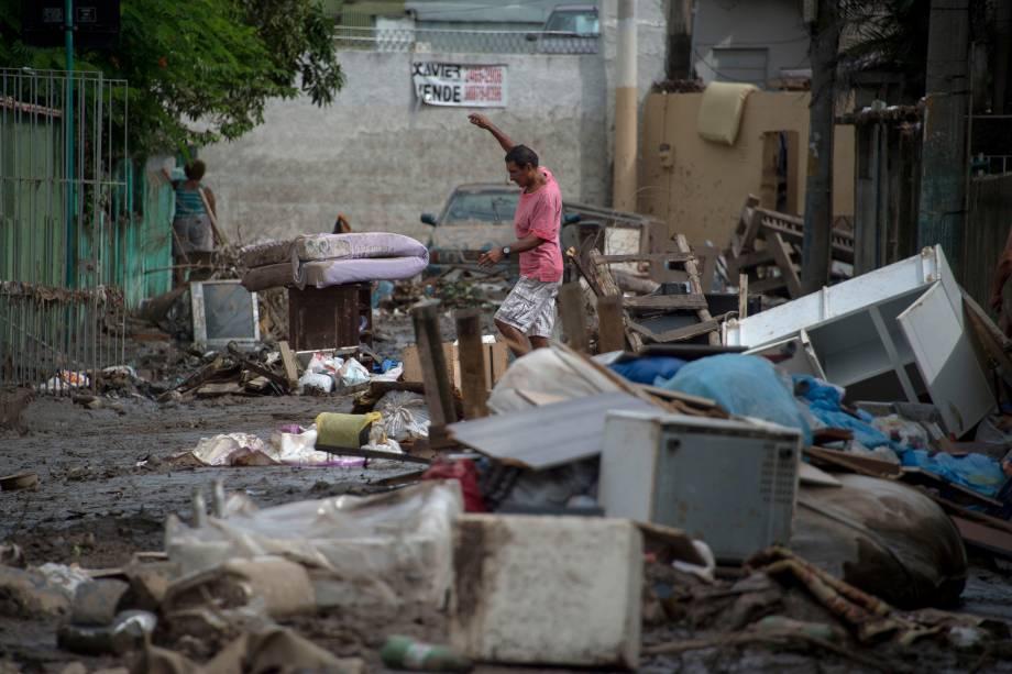 Homem caminha em uma rua coberta de móveis destruídos após enchentes que espalharam lama e estragos no bairro de Bonsucesso, no Rio de Janeiro - 15/02/2018