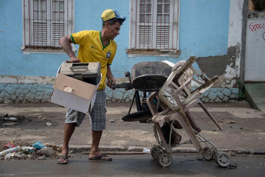 Homem tenta recuperar seus pertences após enchente provocada pelas fortes chuvas em Bonsucesso, no Rio de Janeiro - 15/02/2018