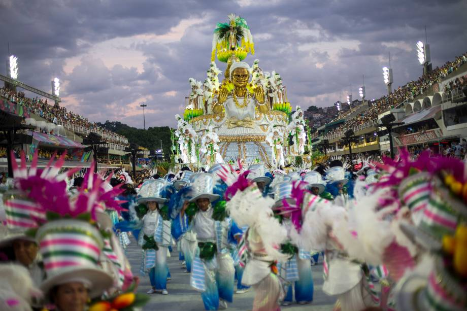 Integrantes da escola de samba Mocidade Indepentende desfilam à medida que o sol nasce após a primeira noite do Carnaval na Marquês de Sapucaí - 12/02/2018