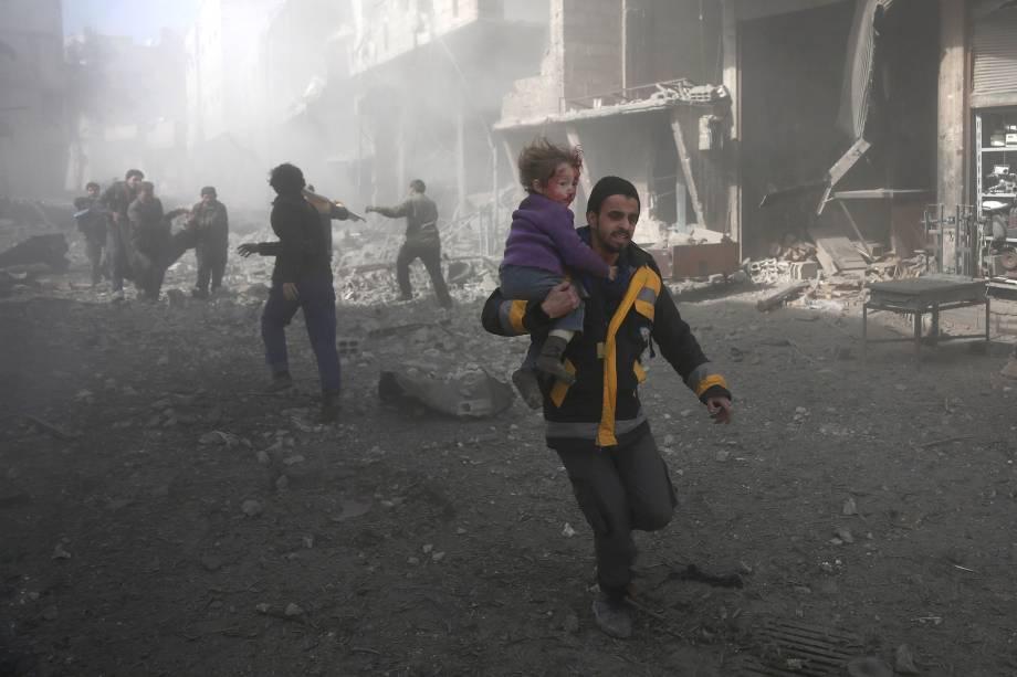 Homem carrega uma criança ferida em bombardeios do governo na cidade rebelde de Hamouria, na região sitiada de Ghouta Oriental, nos arredores da capital Damasco - 19/02/2018