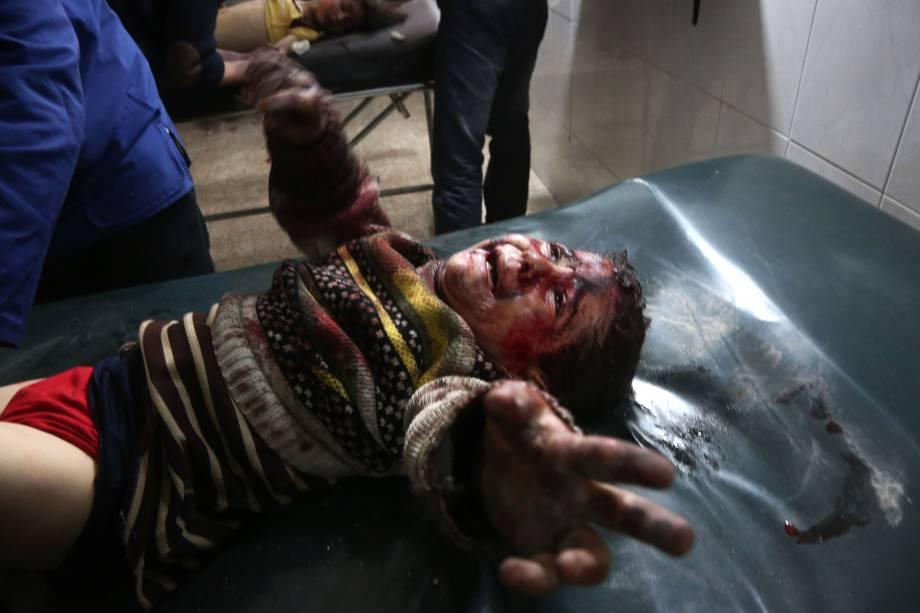 Criança síria ferida em bombardeios atribuídos às forças do governo chora enquanto recebe tratamento em um hospital na cidade rebelde de Hamouria, na região sitiada de Ghouta Oriental, nos arredores da capital, Damasco - 19/02/2018
