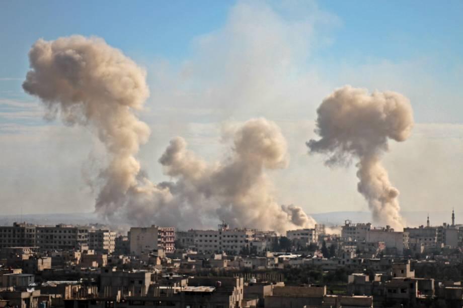 Fumaça sobe dos edifícios após o bombardeio na aldeia de Mesraba, na região de Ghouta ocupada por rebeldes e sitiada nos subúrbios da capital Damasco - 19/02/2018