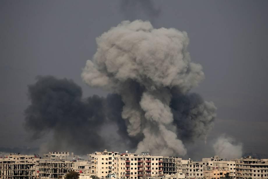 Nuvens de fumaça surgem na sequência de um poderoso ataque aéreo do regime sírio contra o reduto rebelde de Hamouria, na região sitiada de Ghouta Oriental - 20/02/2018