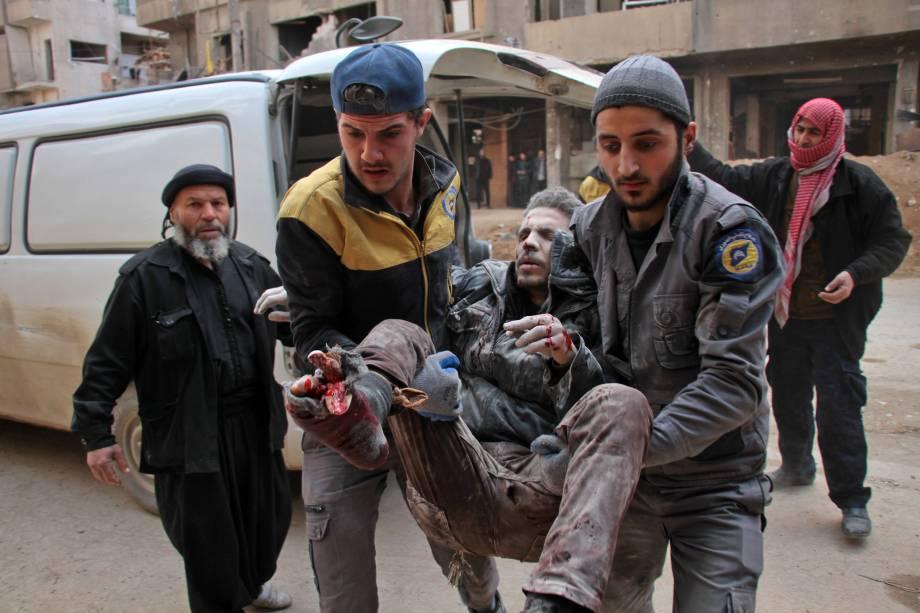 Homem é socorrido por membros da defesa civil da Síria. Os ataques aéreos do regime após três dias de intensos bombardeios no reduto rebelde de Ghouta já deixaram ao menos 300 mortos - 20/02/2018