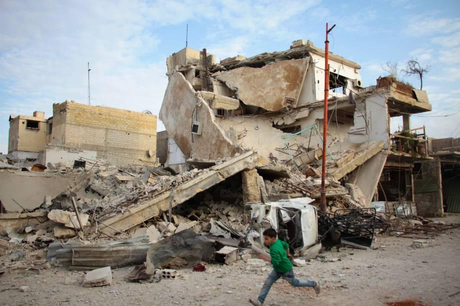 Menino corre em frente a edifício completamente destruído durante ataques aéreos das forças do regime sírio na cidade rebelde de Douma, na região sitiada de Ghouta Oriental - 20/02/2018