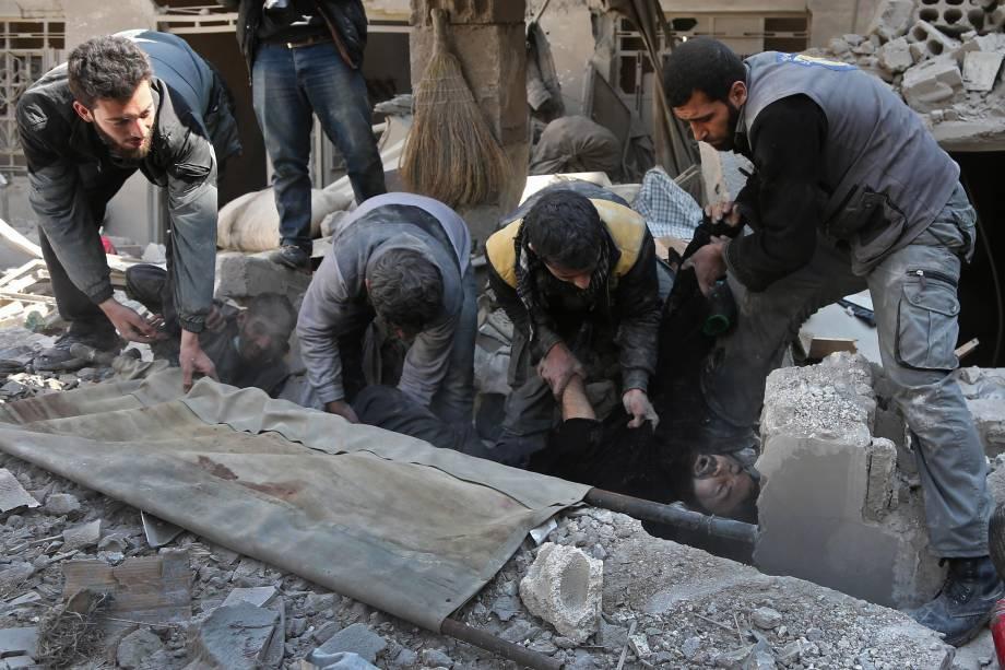 Membros da defesa civil síria resgatam um homem dos escombros após ataque aéreo das forças do governo no reduto rebelde de Hamouria, na região sitiada de Ghouta Oriental - 21/02/2018