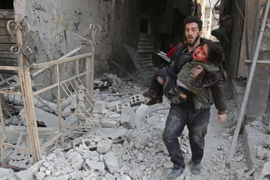 Homem resgata uma criança ferida após ataque aéreo das forças do governo sírio no reduto rebelde de Hamouria, na região sitiada de Ghouta Oriental nos arredores da capital, Damasco - 21/02/2018