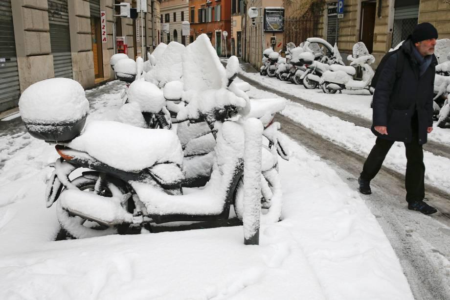 Um homem caminha ao lado de um estacionamento, onde todas as motocicletas estão cobertas de neve, devido à uma onda de frio que congelou a cidade de Roma, na Itália - 26/02/2018