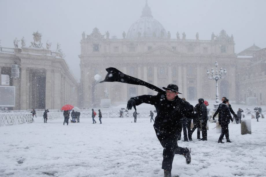 Um padre é visto arremessando uma bola de neve durante uma nevasca na cidade de Roma, na Itália - 26/20/2018