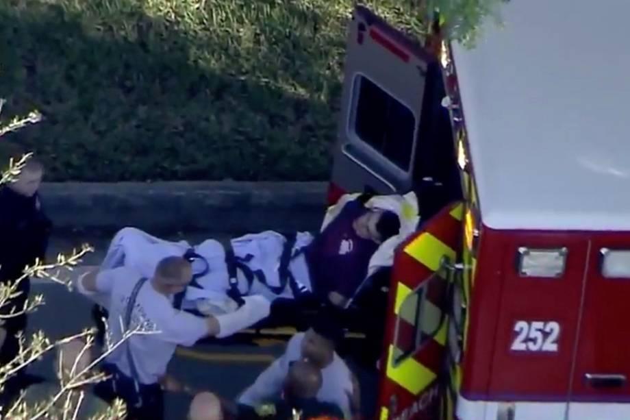 Homem algemado pela polícia é carregado em um veículo paramédico após abrir fogo contra estudantes e professores na Marjory Stoneman Douglas High School em Parkland, Flórida - 14/02/2018