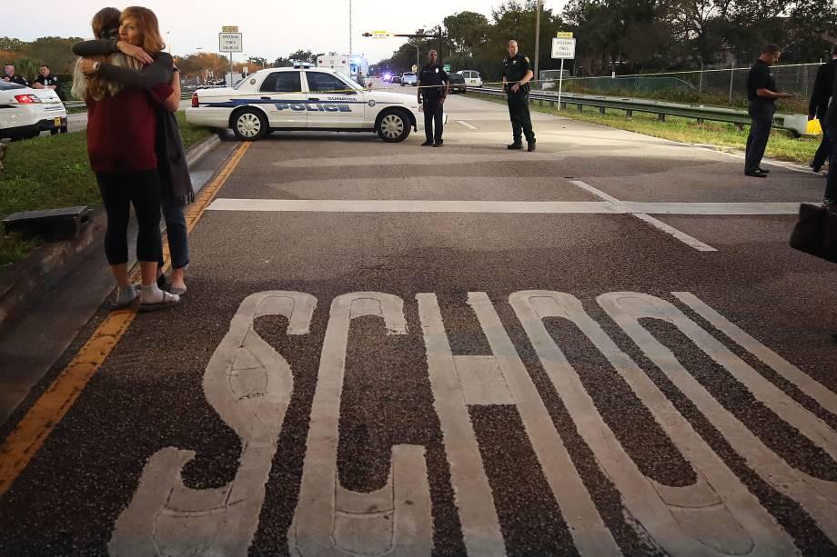 Mulher abraça uma jovem em um ponto de controle da polícia perto da Escola Secundária Marjory Stoneman Douglas, na Flórida onde 17 pessoas foram mortas por um ex-aluno armado - 14/02/2018