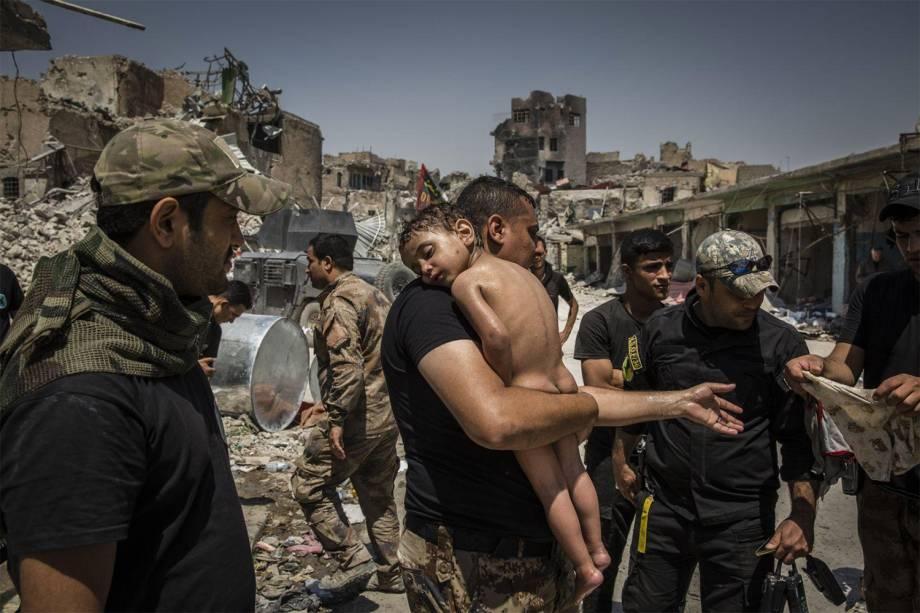 Um garoto não identificado, que foi levado da última área controlada pelo ISIS na Cidade Velha de Mossul por um homem suspeito de ser militante, é carregado pelos soldados iraquianos das Forças Especiais - 12/07/2017
