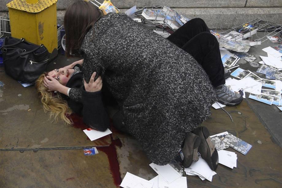 Mulher é vista ajudando uma vítima ferida no chão depois que Khalid Masood dirigiu seu carro na direção de pedestres matando quatro, além de um policial na Westminster Bridge em Londres, Grã-Bretanha - 22/03/2017
