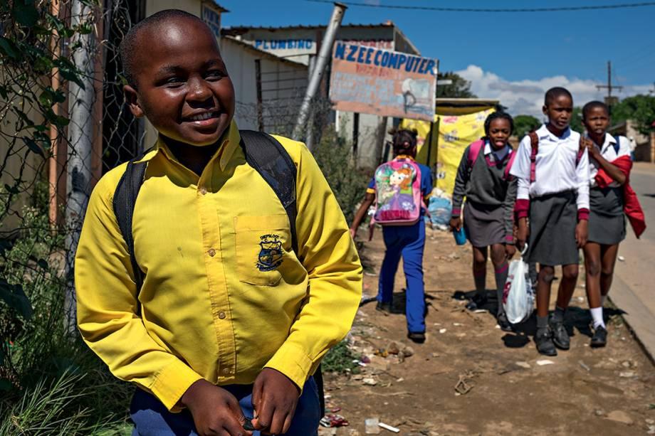 """SORRISO E SILÊNCIO - Aos 14 anos, o estudante Tshepo Natamela (à esq.) conta que sua família sentiu na pele os efeitos do regime de segregação racial, mas prefere não levantar o assunto em casa. """"É um machucado que ficou para eles. Para mim, não, a vida é boa, é leve, e eu adoro falar dela"""""""