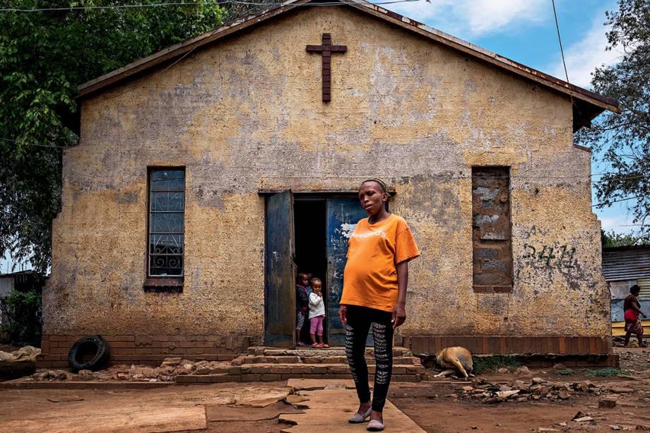 """À espera do voo alto - Mãe de uma menina de 6 anos, a professora Fisokuhle Mdzebu, de 29 anos, exibe o barrigão de nove meses do segundo filho, em frente à igreja onde funciona a creche em que trabalha: """"Meus pais não pisaram na escola, eu parei antes da faculdade, mas meus filhos certamente terão muito mais chances"""", diz"""