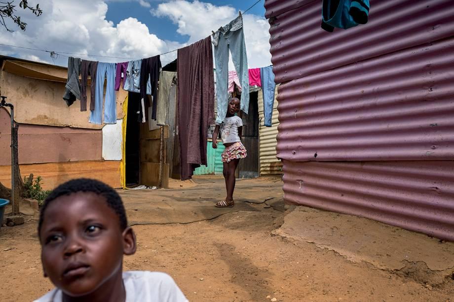 """CONTRASTE - Em meio às cenas de pujança, brotam em Soweto pequenas favelas como esta, onde moram as irmãs Siphokazi, de 4 anos (à frente), e Soyama, 6 anos (no fundo), junto com a mãe e a avó: na esteira do desemprego, muita gente que subiu experimenta agora queda na renda. Soyama, com jeito meio adulto, acredita: """"Sei que a situação vai melhorar"""""""