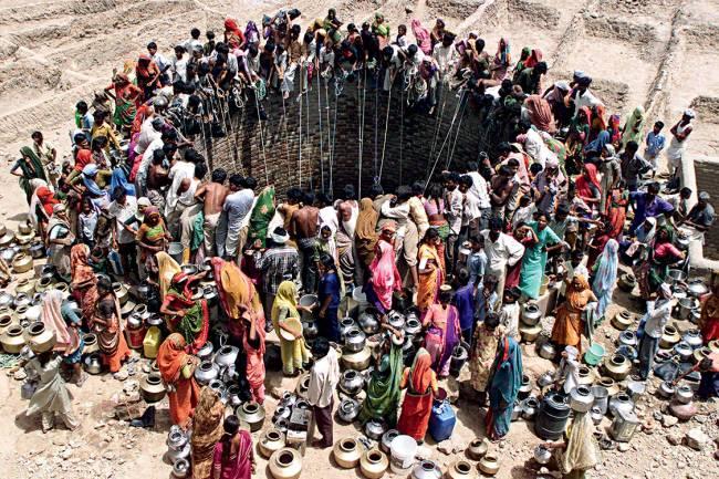 Peregrinação por água – Moradores do vilarejo Natwarghad aglomeram-se ao redor de um poço.