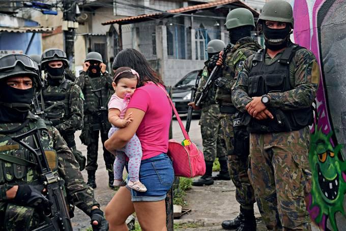 Sob intervenção – Moradora da Vila Kennedy, no Rio, passa pelos soldados: a população das favelas no meio da guerra