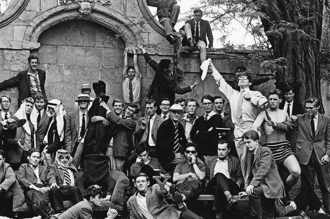 21 anos – Em Oxford (de pé, com camisa branca e lenço na mão), pouco antes de descobrir sua doença