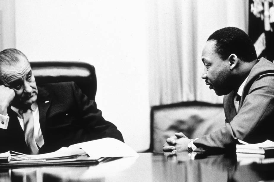 """O Presidente Lyndon B. Johnson discute a Lei dos Direitos de Voto com o ativista de direitos civis Martin Luther King Jr. O ato, parte do programa """"Great Society"""", do presidente Johnson, triplicou o número de eleitores negros no sul, que antes haviam sido prejudicados por leis de inspiração racial, em 1965"""