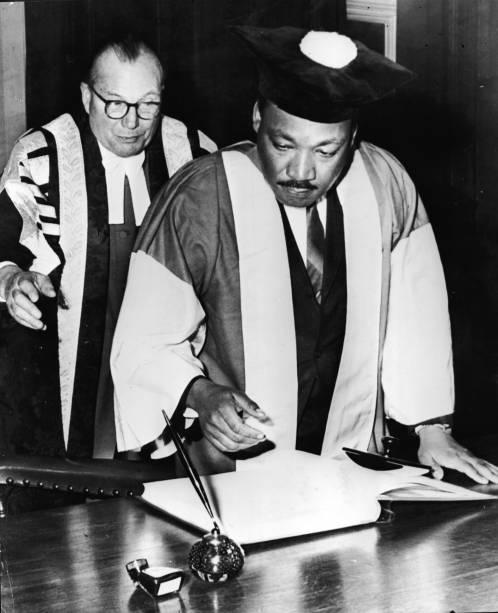 Martin Luther King, Jr., assistido pelo Dr. Charles Bousenquet, assina o curso de graduação na Universidade de Newcastle depois de receber um título honorário de Doutor em Direito Civil, na Inglaterra - 14/11/1967