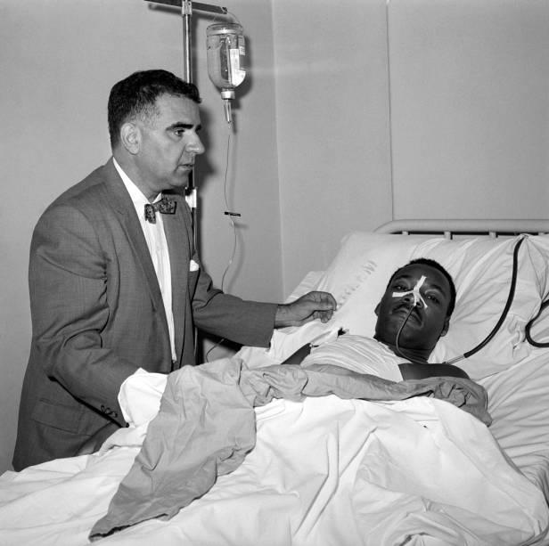 Após uma ciriurgia de 3 horas para remover uma faca do peito de Martin Luther King Jr., o Dr. Emil A. Naclerio fica ao seu lado no leito do hospital Harlem - 20/09/1958