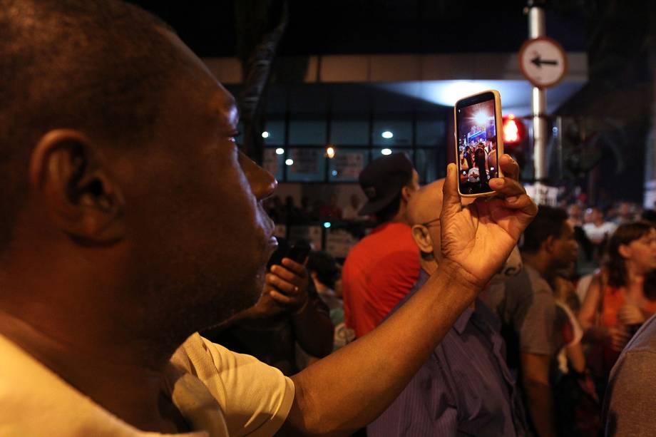 Homem tira foto com o celular de movimentação nos arredores do sindicato