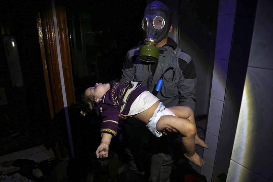Imagem divulgada pelos Capacetes Brancos da Defesa Civil Síria, mostra uma criança sendo resgatada após um ataque de armas químicas na cidade de Douma, perto de Damasco, na Síria - 08/04/2018
