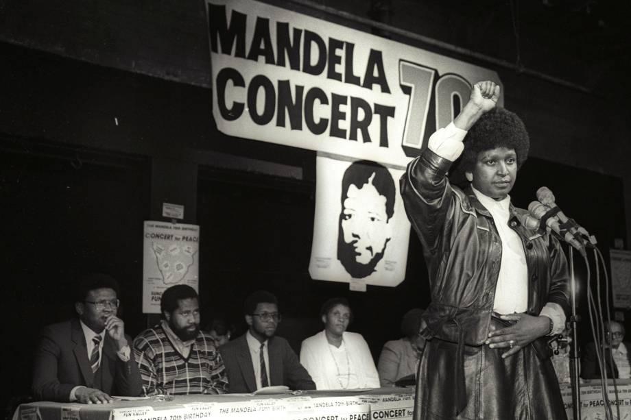 Winnie Mandela levanta a mão em uma saudação ao poder negro após anunciar que um enorme show pop será realizado para marcar o 70º aniversário de seu marido, o líder nacionalista negro encarcerado Nelson Mandela - 17/07/1988