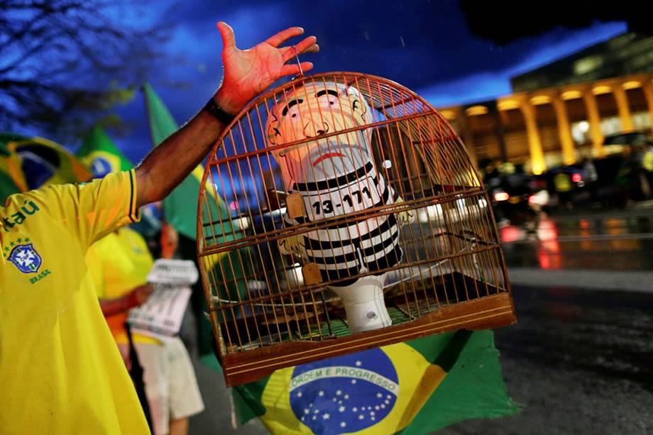 Manifestante mostra pixuleco em uma gaiola durante protesto contra o ex-presidente Lula, em Brasília