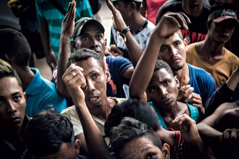 Fome e desalento - Homens se amontoam para receber refeição distribuída por voluntários em Boa Vista
