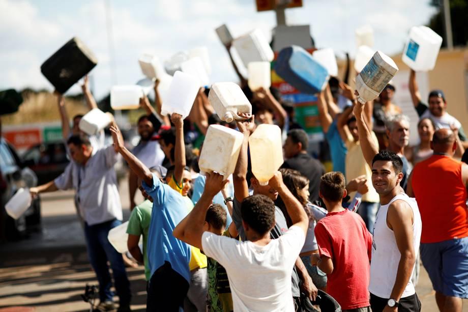 Pessoas são vistas carregando galões vazios próximas de posto de combustíveis em Brasília (DF) - 25/05/2018