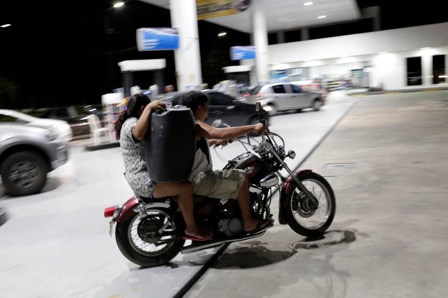 Mulher deixa um posto de combustível carregando galão de gasolina sobre uma moto em Manaus (AM) - 25/05/2018