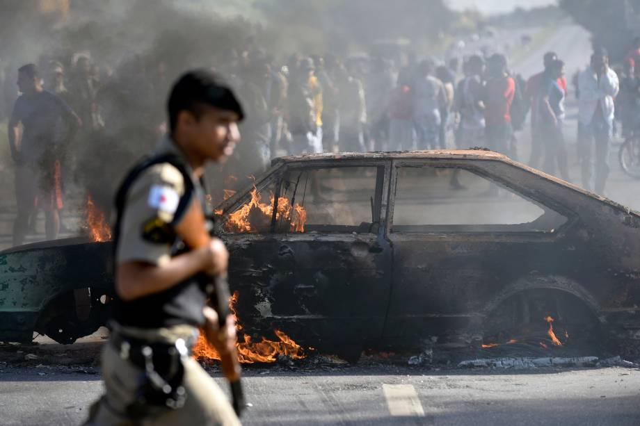 Policial passa por um carro incendiado por manifestantes que protestam contra os preços dos combustíveis no bairro de São Marino, em Ribeirão das Neves, região metropolitana de Belo Horizonte (MG) - 25/05/2018